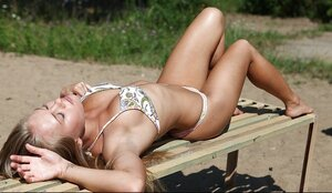 Fascinating young and fresh woman with pretty breasts lies on an outdoor bench sunbathing