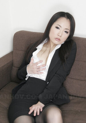 Oriental secretary sits down on the sofa and moreover furthermore doffs white panties and moreover furthermore spreads legs
