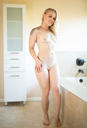 Gorgeous blonde with tattoos on shoulders poses nude in the bathroom