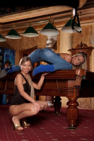 Cheerful broad and furthermore blonde in denim overalls pose and furthermore caress by the pool table